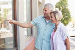 Happy mature couple window shopping in the city Stock Photos