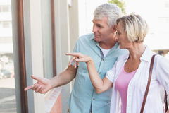 Happy mature couple window shopping in the city Royalty Free Stock Photo
