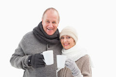 Happy mature couple in winter clothes holding mugs Stock Photos