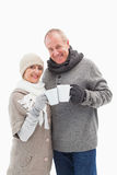 Happy mature couple in winter clothes holding mugs Stock Photo