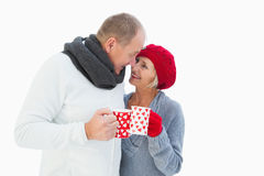 Happy mature couple in winter clothes holding mugs. On white background Royalty Free Stock Photo