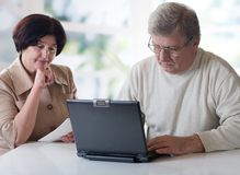 Happy mature couple working on laptop Royalty Free Stock Image