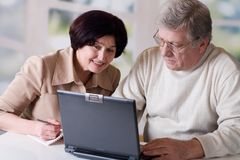 Happy mature couple working on laptop Stock Photography