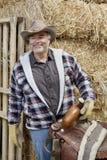 Happy mature cowboy holding saddle Stock Images