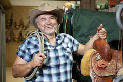 Happy mature cowboy with saddle and rope in feed store Royalty Free Stock Image