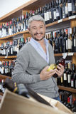 Happy Mature Customer Holding Wine Bottles. Portrait of happy mature customer holding wine bottles in store Royalty Free Stock Photo