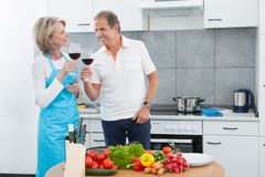 Happy mature drinking wine in kitchen royalty free stock photos