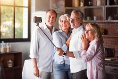 Happy mature family taking selfies with smartphone in the kitchen Royalty Free Stock Images