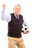 A happy mature fan with football gesturing with his hand Stock Image