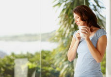 Happy mature female holding a coffee cup Stock Images