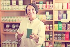 Happy mature female seller  holding dietary nutrients Royalty Free Stock Images