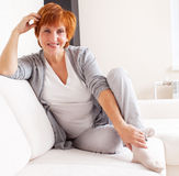 Happy mature female on sofa Stock Photos