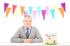Happy mature gentleman with party hat and a birthday cake Stock Image