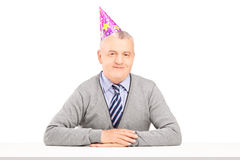 Happy mature gentleman with party hat Royalty Free Stock Photography