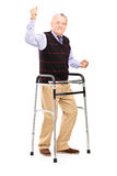 Happy mature gentleman with walker gesturing happiness Stock Photography