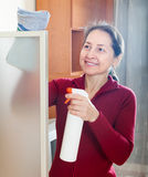 Happy mature girl cleans glass Royalty Free Stock Images