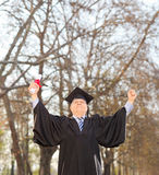 Happy mature graduate holding diploma outdoors Royalty Free Stock Images