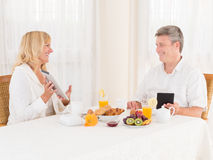 Happy mature healthy couple using tablets and ebook ereaders at breakfast. Happy mature healthy couple using tablet computers and ebook ereaders at breakfast Stock Photography