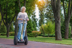 Happy mature lady driving segway royalty free stock photo