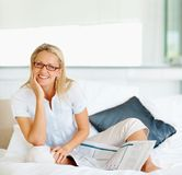 Happy mature lady with newspaper on bed Royalty Free Stock Images