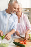 Happy mature loving couple family cooking salad stock photos