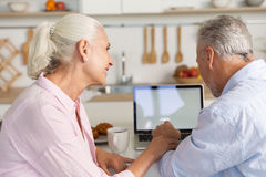 Happy mature loving couple family at the kitchen using laptop Royalty Free Stock Photos