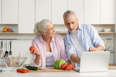 Happy mature loving couple family using laptop and cooking Royalty Free Stock Images