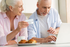 Happy mature loving couple family using laptop holding credit card. Image of happy mature loving couple family standing at the kitchen using laptop computer Royalty Free Stock Image