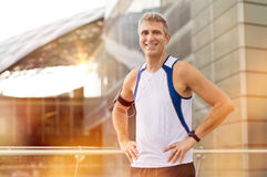 Happy Mature Male Jogger. Portrait Of Happy Mature Male Jogger With Earphone Looking At Camera Outdoor Royalty Free Stock Images