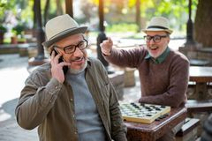 Happy mature male pensioner communicating on cellphone Stock Photo