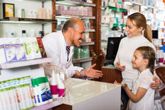Happy mature male pharmacist helping customers. Happy mature male pharmacist wearing white coat standing next to shelves with medicine and helping customers Stock Photography