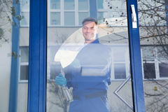 Happy Mature Male Worker Cleaning Glass With Rag. Portrait of happy mature male worker cleaning glass with rag Stock Photos