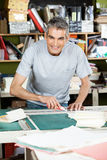 Happy Mature Male Worker Cutting Paper At Table Stock Photography