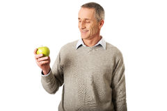 Happy mature man with an apple Stock Image