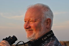 Happy Mature Man with Binoculars at Sunset Stock Images