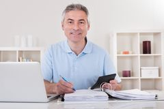 Happy mature man calculating Royalty Free Stock Photo