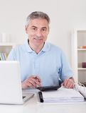 Happy Mature Man Calculating Stock Photography