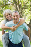 Happy mature man carrying woman at park Royalty Free Stock Photos