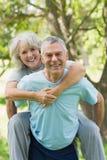 Happy mature man carrying woman at park Royalty Free Stock Photos