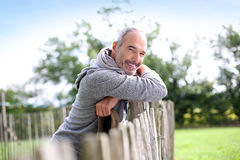 Happy mature man in countryside leaning on wood fence Stock Image