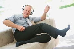 Happy mature man enjoying music on an mp3 player Royalty Free Stock Photo
