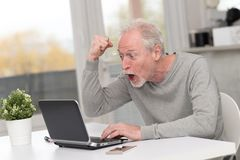 Happy mature man having a good surprise on laptop. Happy mature man having an amazing surprise on laptop stock photo
