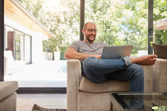 Happy mature man having video call on laptop. Indoor shot of a happy mature man having video call with laptop and earphones while sitting on the couch at home royalty free stock photos