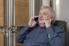 Happy mature man laughing and talking on the phone. At home royalty free stock photography