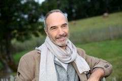 Happy mature man leaning on fence outdoor Stock Image