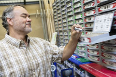 Happy mature man looking at staple pack in store. Happy mature men looking at staple pack in store Stock Photo