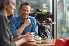 Happy mature man looking to woman with pleasure. Enjoyable meeting. Waist up portrait of happy smiling mature male looking with pleasure to lady while sitting royalty free stock photography
