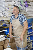 Happy mature man pushing cart in feed store Stock Images