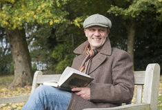 Happy mature man reading a book outdoors in autumn. Stock Image