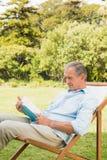 Happy mature man reading book Stock Photo